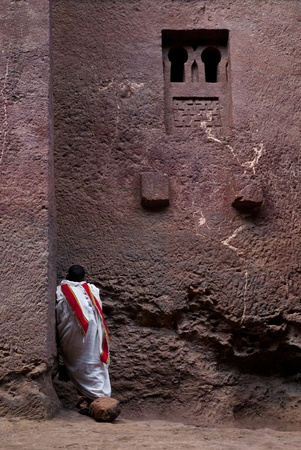 coptic orthodox: coptic priest parying outside church in lalibela ethiopia Editorial