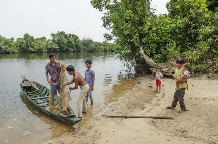 young men fishing in rural cambodia river