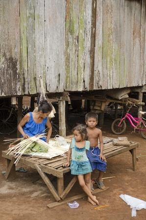 elderly woman weaving basket in cambodia village