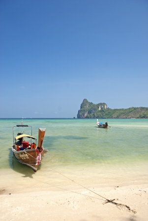 boat on tropical ko phi phi beach in thailand photo