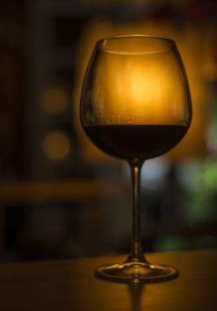 dark interior: red wine glass in cozy dark interior Stock Photo