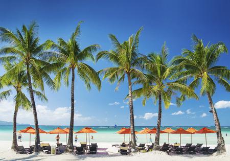 boracay: white beach lounge bar chairs and umbrellas on boracay tropical island in philippines