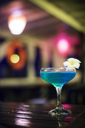 curacao: blue curacao and vodka cocktail drink in dark bar interior Stock Photo