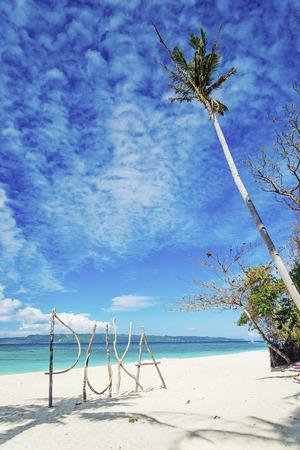 boracay: puka beach wooden sign in boracay tropical island philippines
