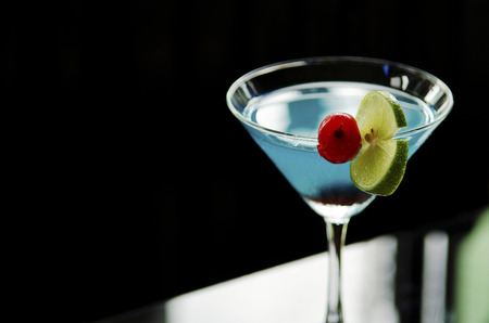 blue cocktail drink with cherry and lime