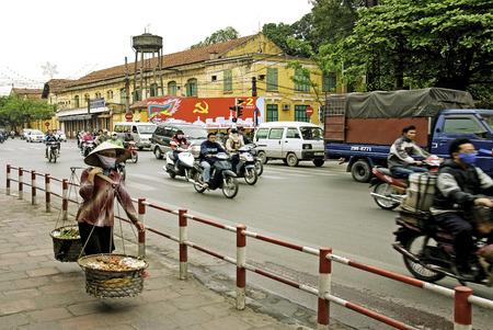 vendor: street scene in central hanoi vietnam with traffic and vendor