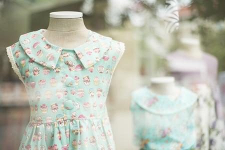colorful dress: young girl fashion colorful dress in childrenswear fashion shop window