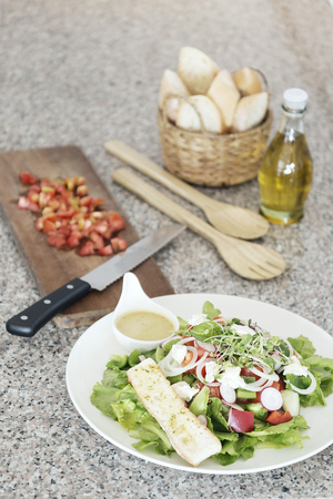 med: healthy greek salad set with bread and olive oil on kitchen surface
