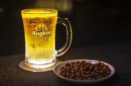 cambodian: glass of popular cambodian angkor beer draft with peanuts in bar Editorial