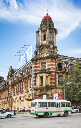 colonial building: british colonial building and city bus in central yangon myanmar