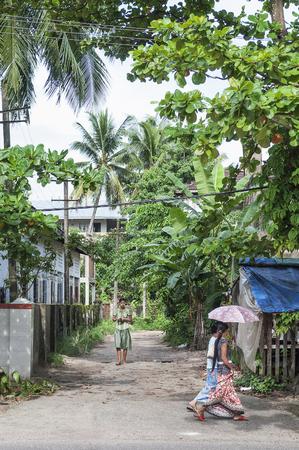 streetscene: girls walking on residential street of yangon myanmar