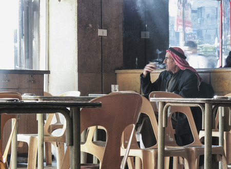 damascus: old arab man smoking inside cafe in damascus syria Editorial