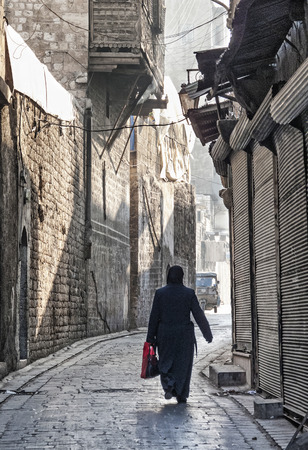 veiled: veiled woman on old town cobbled street in aleppo syria