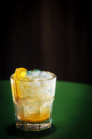 alcohol screwdriver: vodka and orange screwdriver classic cocktail drink on green gambling table at night
