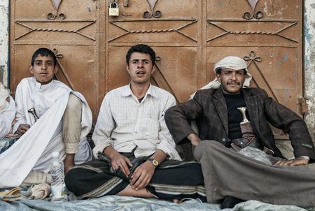 street drug: young arab men chewing khat qat narcotic drug leaves in sanaa yemen street