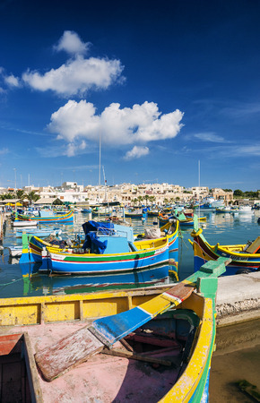 famous industries: marsaxlokk harbour and traditional mediterranean fishing boats in malta island