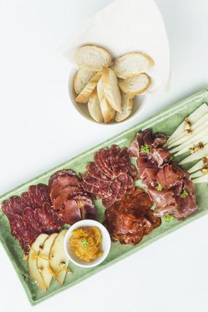 carnes: spanish serrano ham chorizo sausage smoked meats cheese tapas sharing platter set with bread Foto de archivo