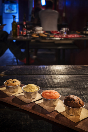 mixed freshly baked muffins on table in cozy coffeeshop interior Stok Fotoğraf