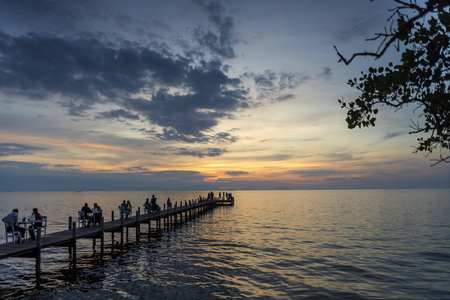 tourists view sunset by pier in kep town on cambodia coast Editorial