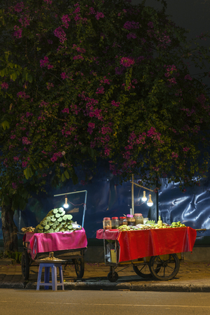 local fruit and snack food stand on phnom penh cambodia street at night