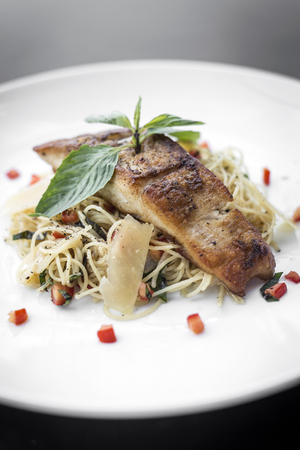 fresh cod fish fillet on mixed vegetable and parmesan spaghetti pasta 免版税图像