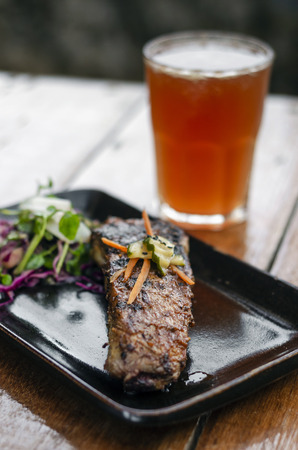 marinated grilled barbecue pork rib with salad and pickled vegetables set with michelada cocktail drink Stockfoto