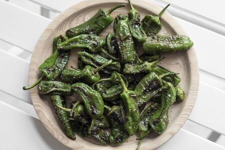 pimientos padron grilled spanish green chilli peppers tapas snack on plate in rustic santiago de compostela restaurant
