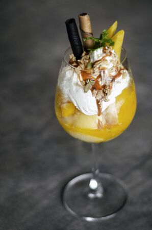 organic mango and passion fruit tropical ice cream sundae in wine glass