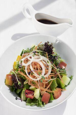 fresh organic mixed vegetable vegan Garden Salad with Vinaigrette sauce on white table 免版税图像