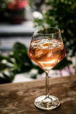 traditional french 'Piscine' rose wine spritzer with orange cocktail drink on table outside