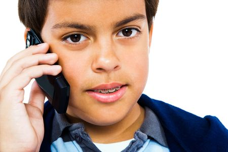 Boy talking on a mobile phone isolated over white photo