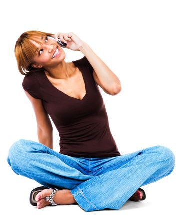 telecommunicating: Woman talking on a mobile phone isolated over white