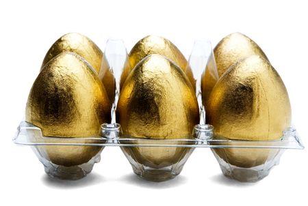 Golden eggs in an egg carton isolated over white photo