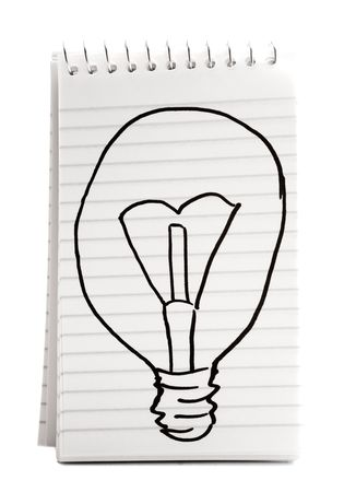 Sketch of a light bulb on a spiral notebook isolated over white photo