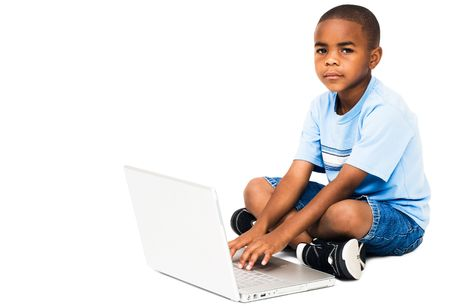telecommunicating: Portrait of a boy working on a laptop isolated over white