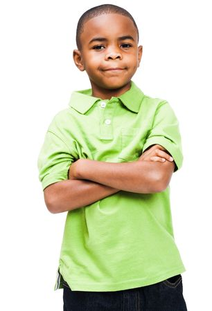 Smiling boy standing with his arms crossed isolated over white Imagens