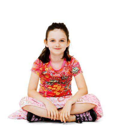 Lachend meisje zittend op de vloer geïsoleerd over wit Stockfoto
