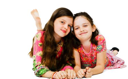 Portrait of two girls smiling and posing isolated over white