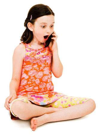 Surprised girl talking on a mobile phone isolated over white photo