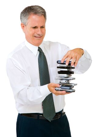 telecommunicating: Businessman holding a stack of phones isolated over white