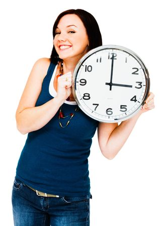 Caucasian woman holding a clock isolated over white Фото со стока