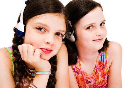 Portrait of girls listening to music on headphones isolated over white