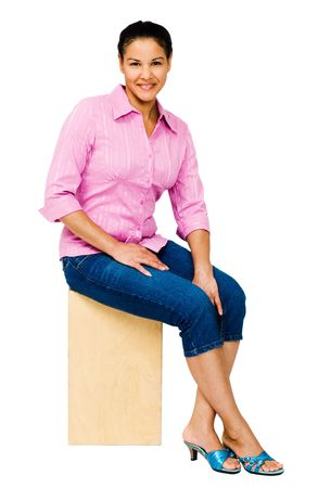 Smiling young woman sitting on a stool isolated over white Stock Photo - 5338856