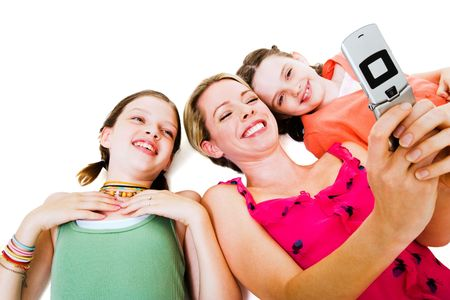 telecommunicating: Woman lying with her daughters and photo messaging isolated over white