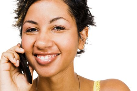 Woman talking on a mobile phone and smiling isolated over white photo