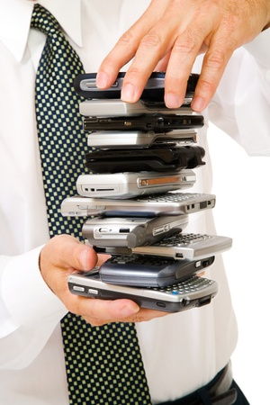 telecommunicating: Close-up of a businessman holding a stack of phones isolated over white Stock Photo
