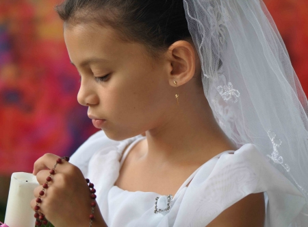 girl with candle and rosary beads photo