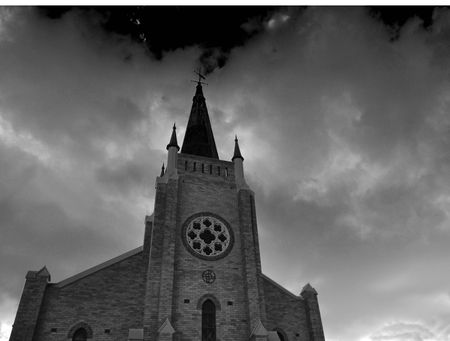 old church with hravy clouds in the sky photo