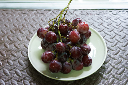 Bunches of fresh ripe red grapes on the dish. Ancient style, a beautiful background with a branch of blue grapes. Red wine grapes. dark grapes, blue grapes, wine grapes Foto de archivo