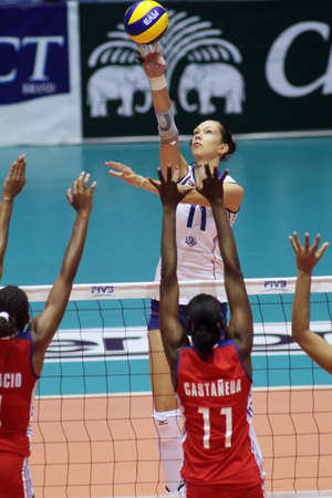 nakhon pathom: nakhon pathom, thailand, august 5, 2011– ekaterina gamova (white jersey ),russian female volleyball player spikes the ball over blocking of cuba players leanny castaneda simon (red  jersey, no.11 )at the first game  for 2011 fivbworld grand prix